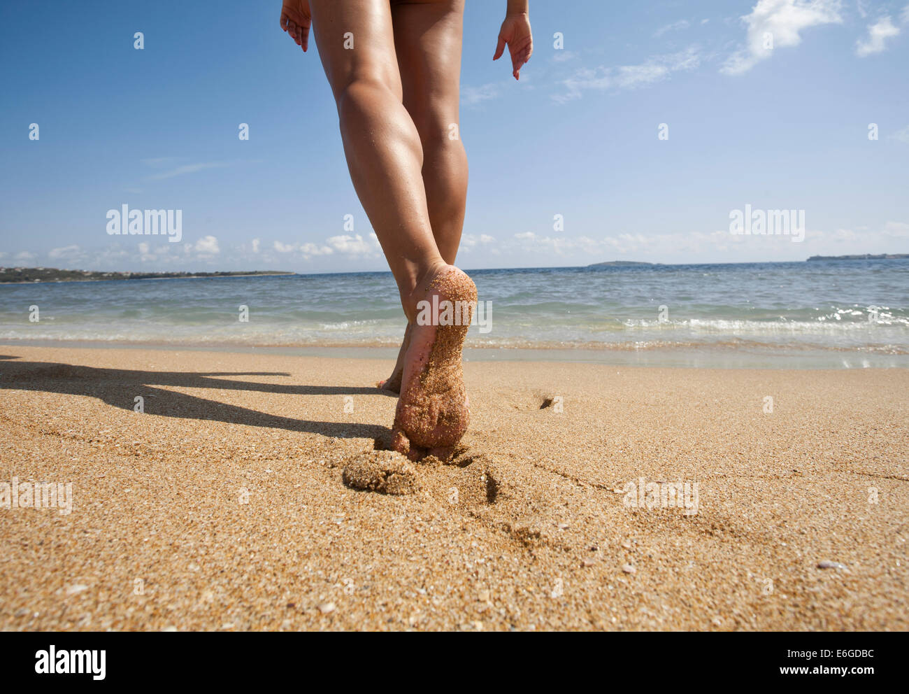 Young woman walking alone on sand beach. Closeup detail of ...