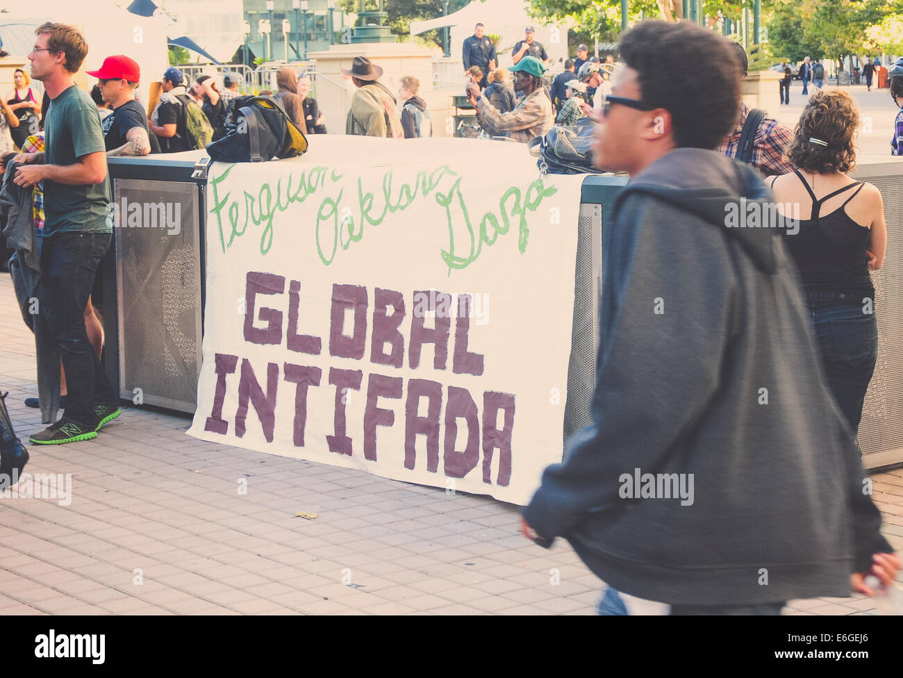 At a protest in Oakland protesters gather around a sign in solidarity with the Palestinian people. - Stock Image