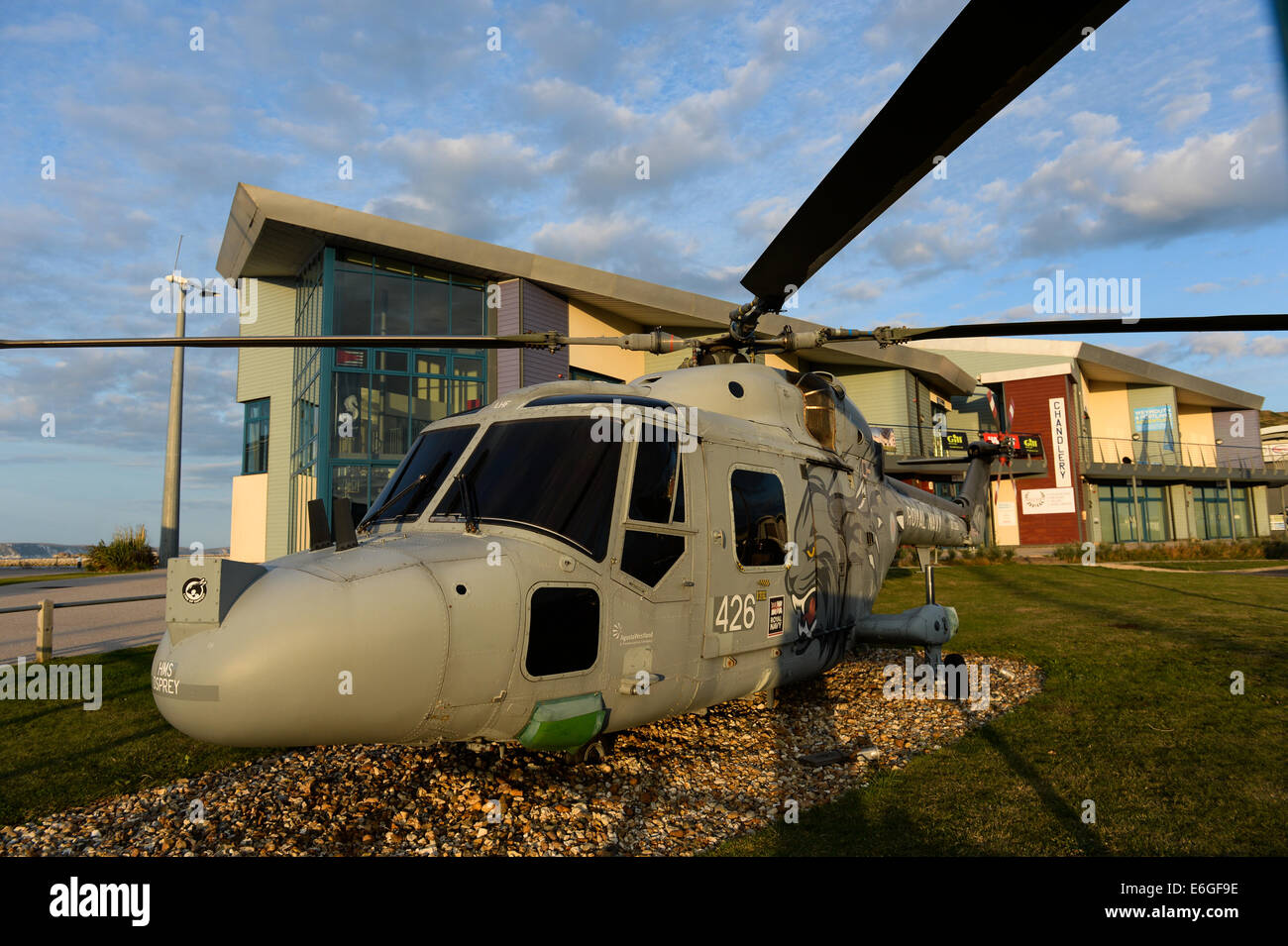 Main entrance to Portland Marina, UK, with a lynx helicopter on display that once flew from the former base, now - Stock Image
