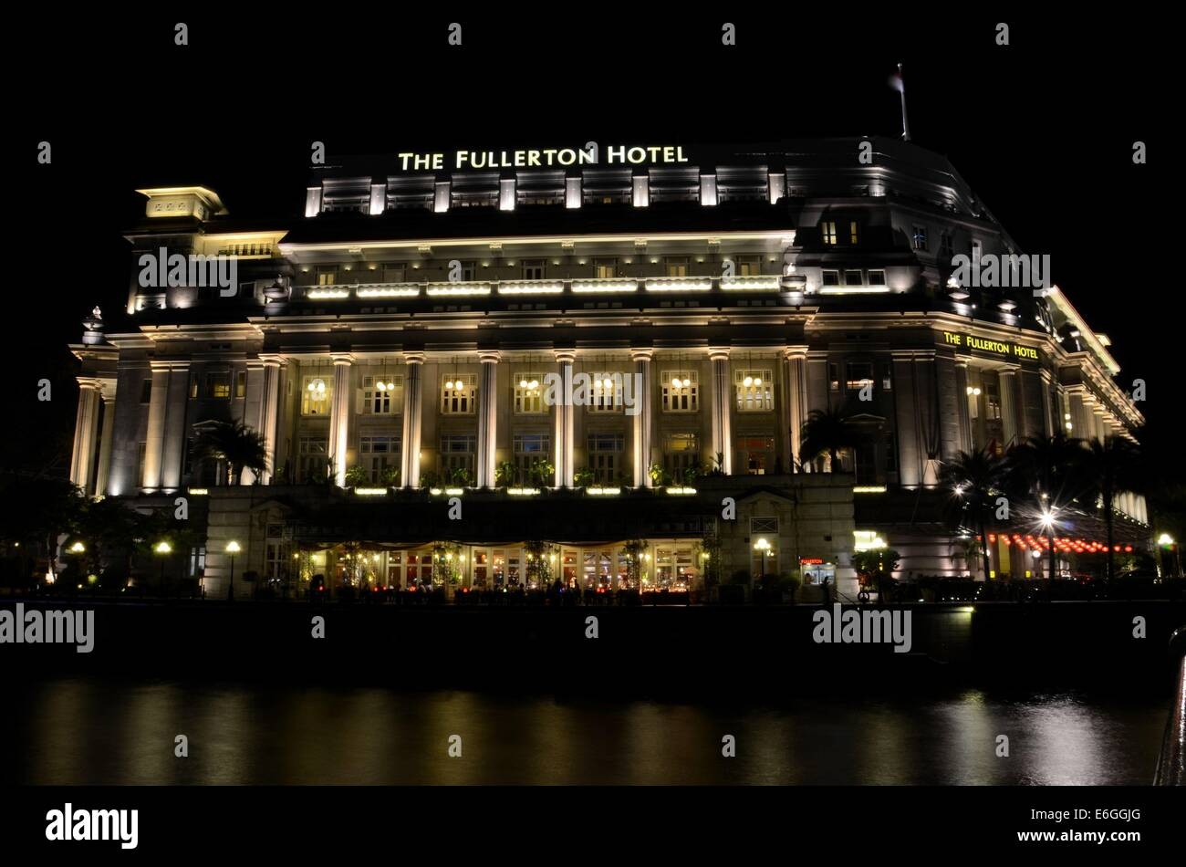 Night shot of Fullerton Hotel (former General Post Office Building) building in Singapore River's Boat Quay - Stock Image
