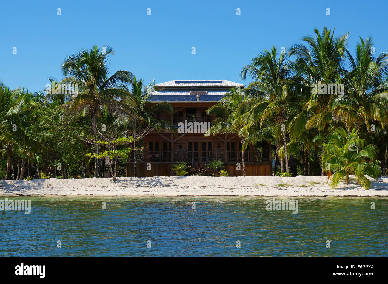 off-grid beach house with solar panels on the roof and tropical vegetation on an island of the Caribbean sea, Panama - Stock Image