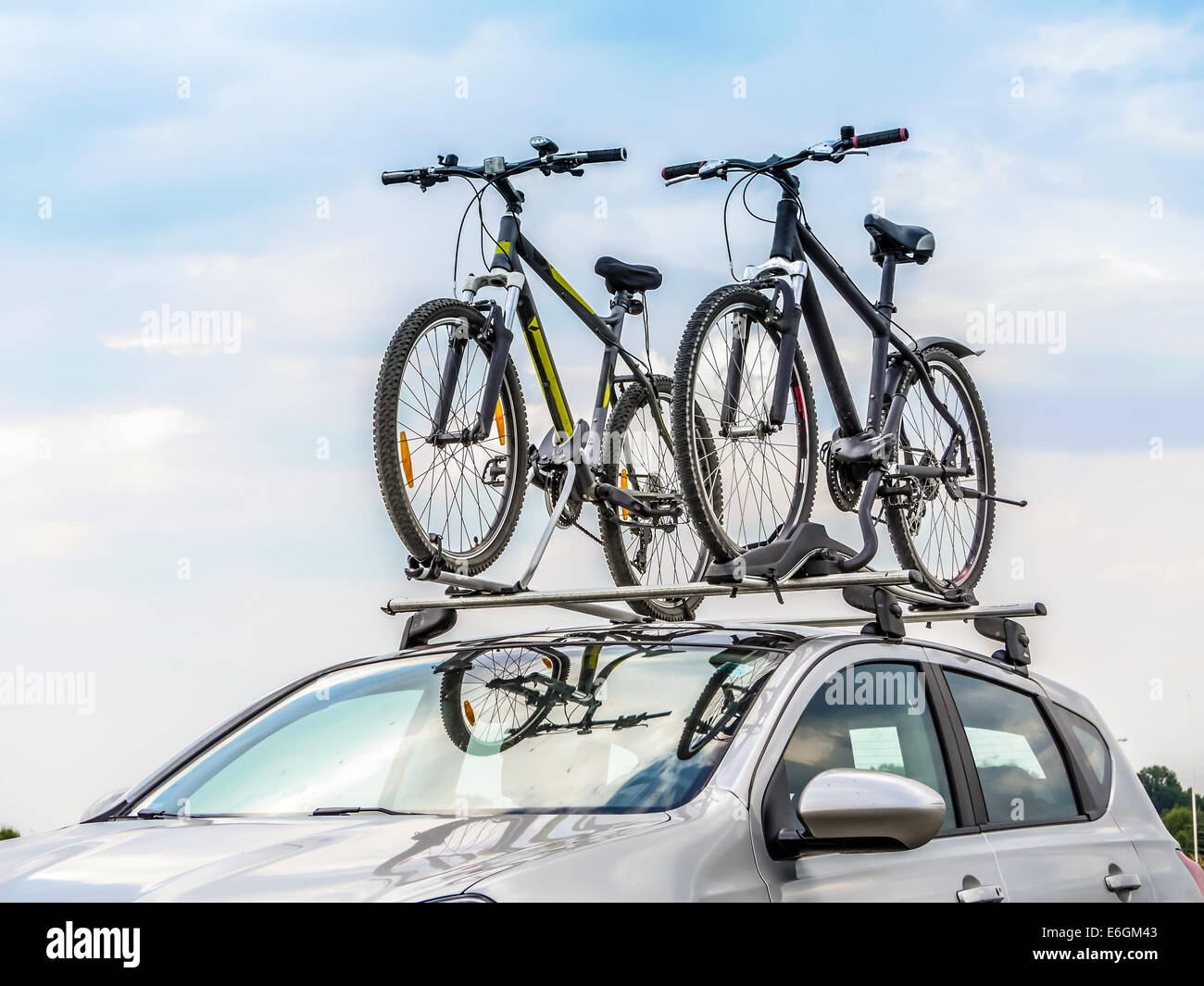 Passenger car with two bicycle mounted to the roof - Stock Image