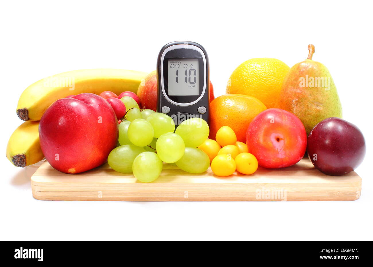 Glucose meter and fresh ripe fruits lying on wooden cutting board, concept for healthy eating and diabetes. Isolated - Stock Image