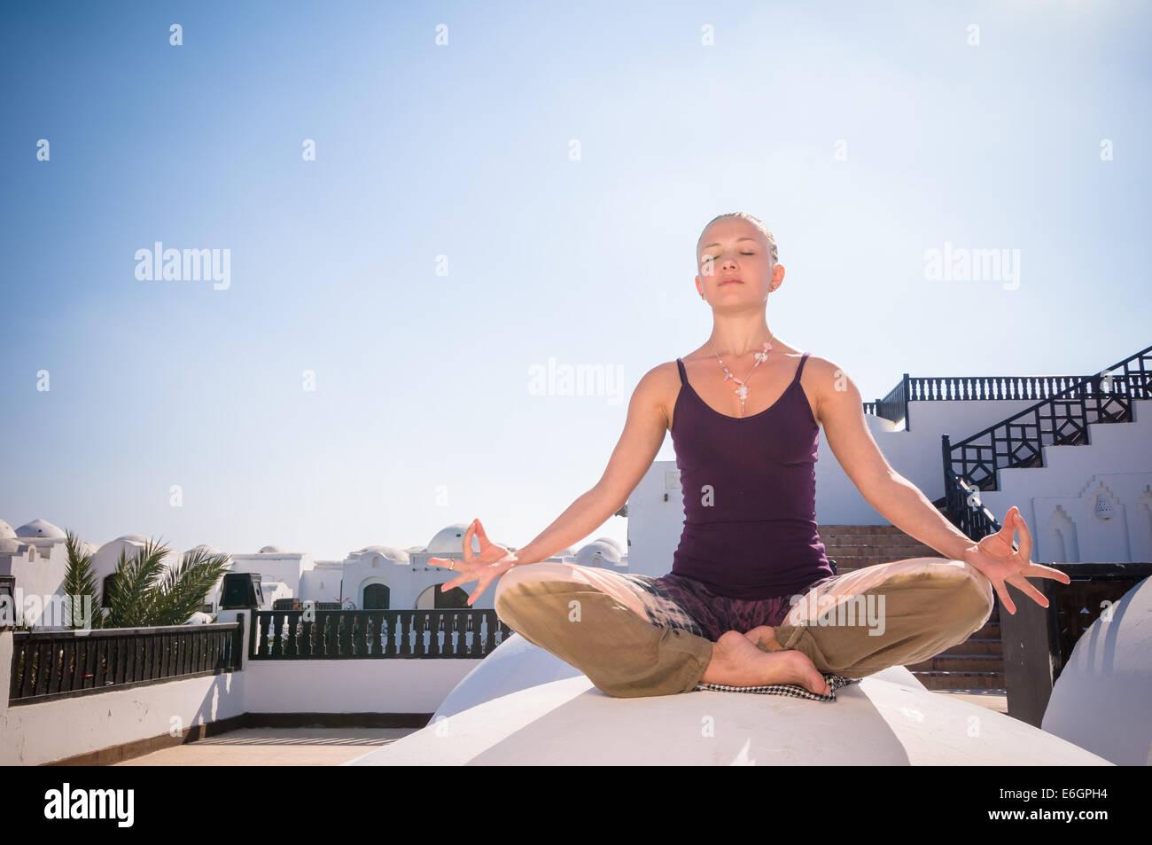 Attractive redhair woman practicing Vinyasa yoga outdoors Stock Photo