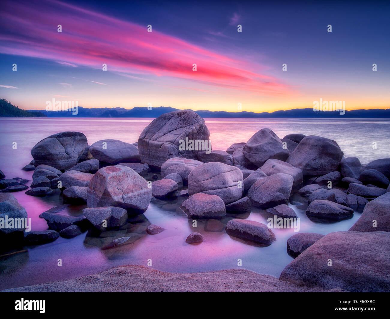 Boulder rocks and sunset on shoreline of Chimney Beach. Lake Tahoe, Nevada - Stock Image