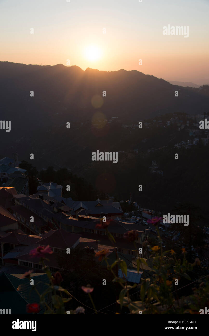 The evening sun setting behind the Himalayan foothills in Shimla, Himachal Pradesh, India, - Stock Image