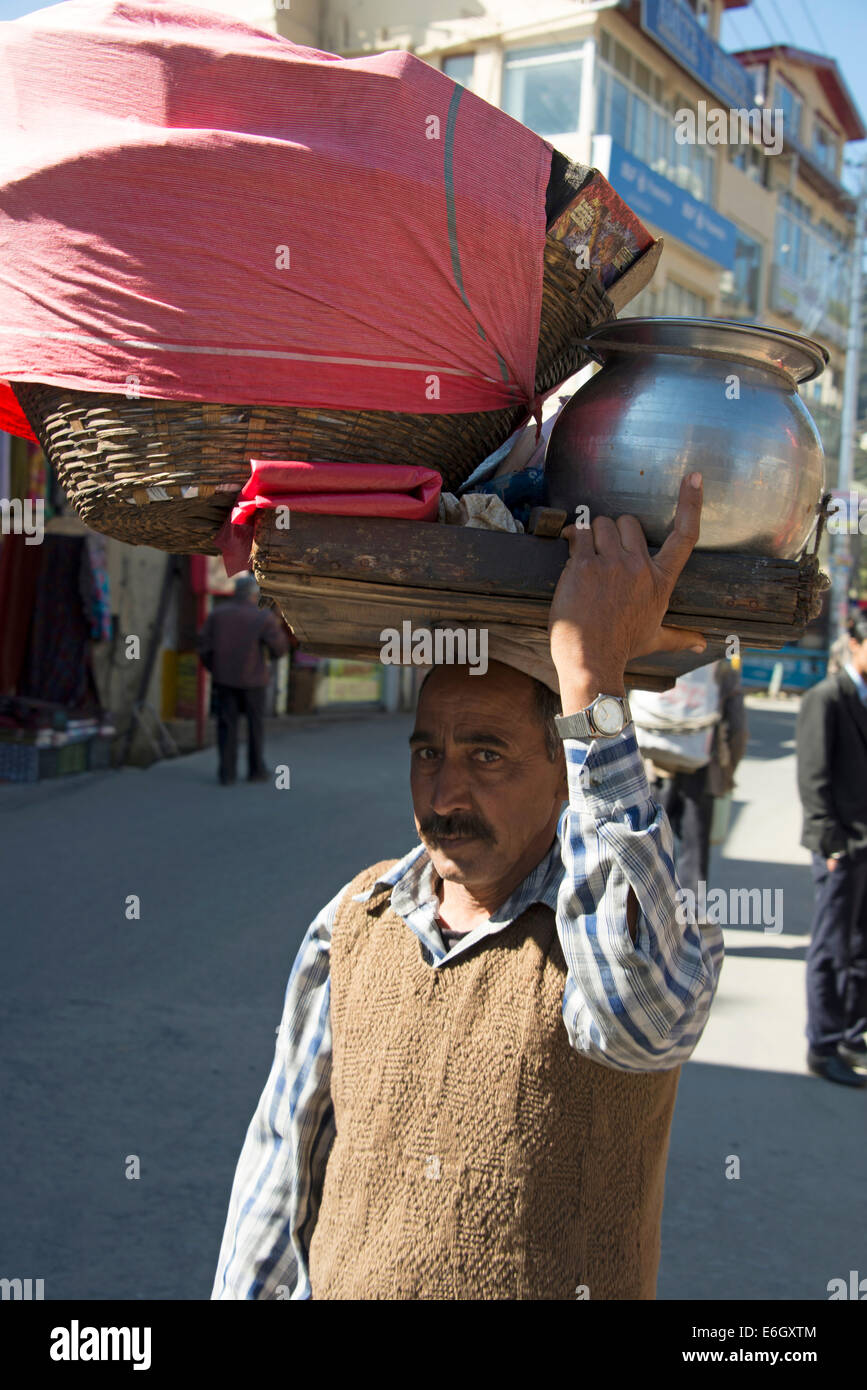 A man carrying his wares in Shimla in Himachal Pradesh,India - Stock Image