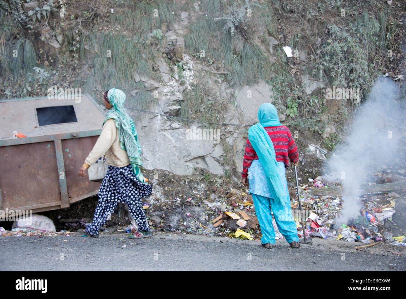Two Asian women burning rubbish beside a main road near Shimla in Himachal Pradesh, - Stock Image