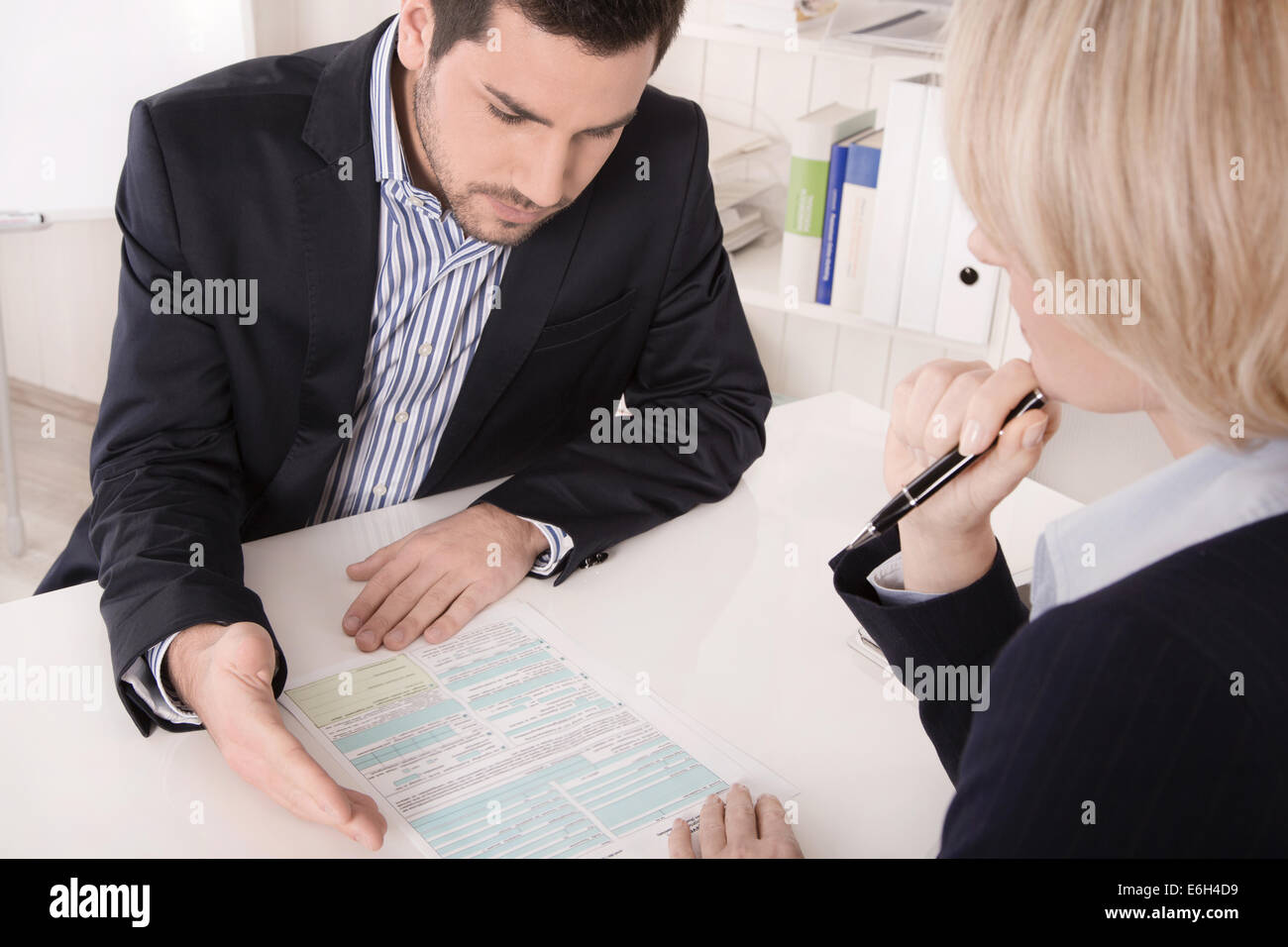 Adviser sitting in a meeting with a blank on the table explaining something his colleague. - Stock Image