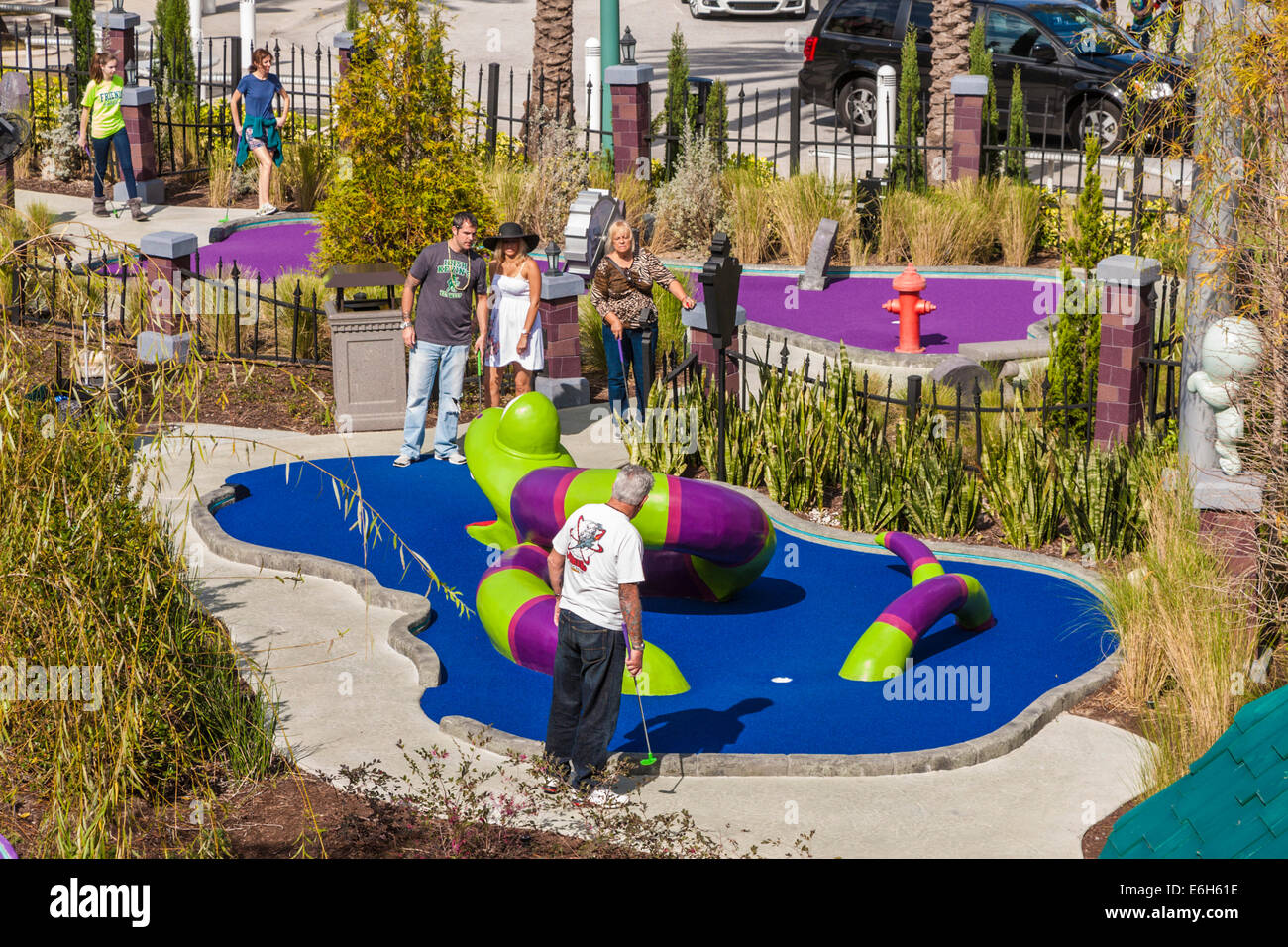Teens and adults playing game of putt-putt golf at Universal Studios in Orlando, Florida - Stock Image