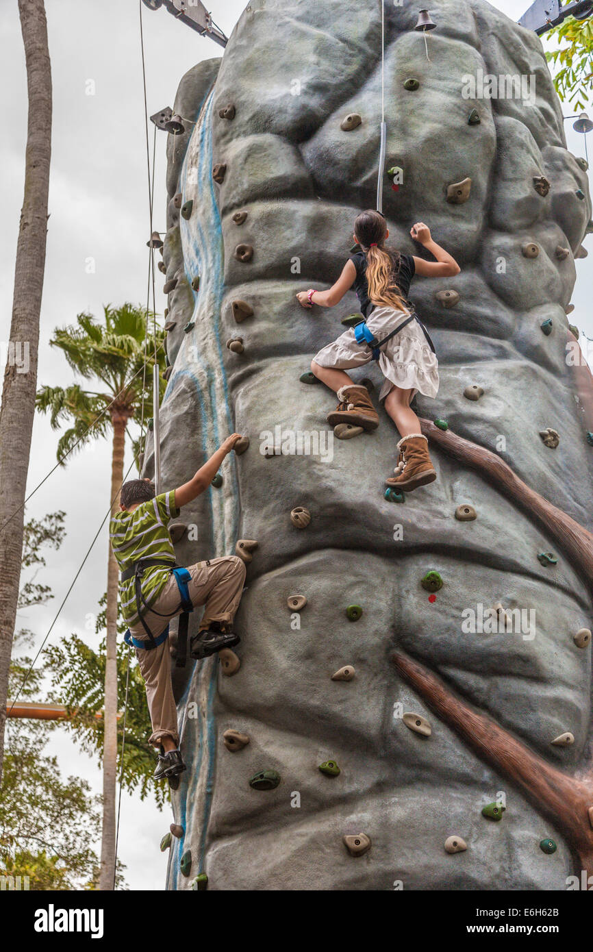 Children climbing rock wall in Jurassic Park attraction at Universal Studios Islands of Adventure theme park in - Stock Image