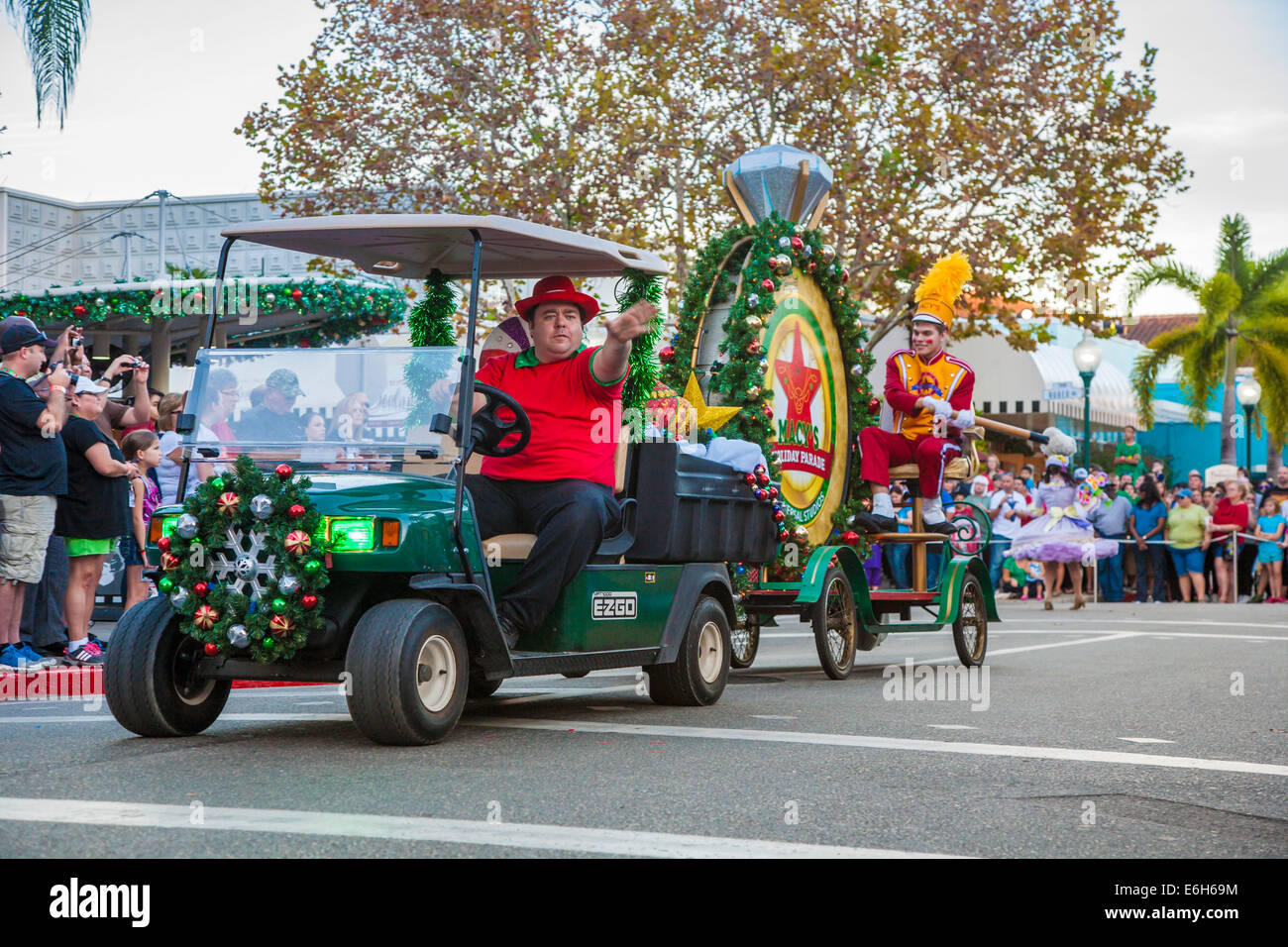 Man driving decorated golf cart pulling large bass drum in Macy's Holiday Parade at Universal Studios in Orlando, - Stock Image