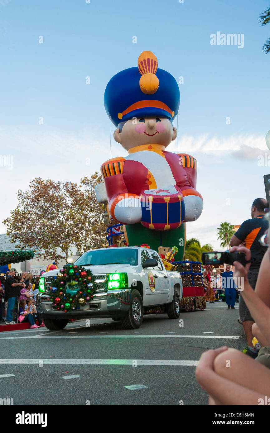 Drummer balloon float pulled by decorated truck in Macy's Holiday Parade at Universal Studios, Orlando, Florida - Stock Image