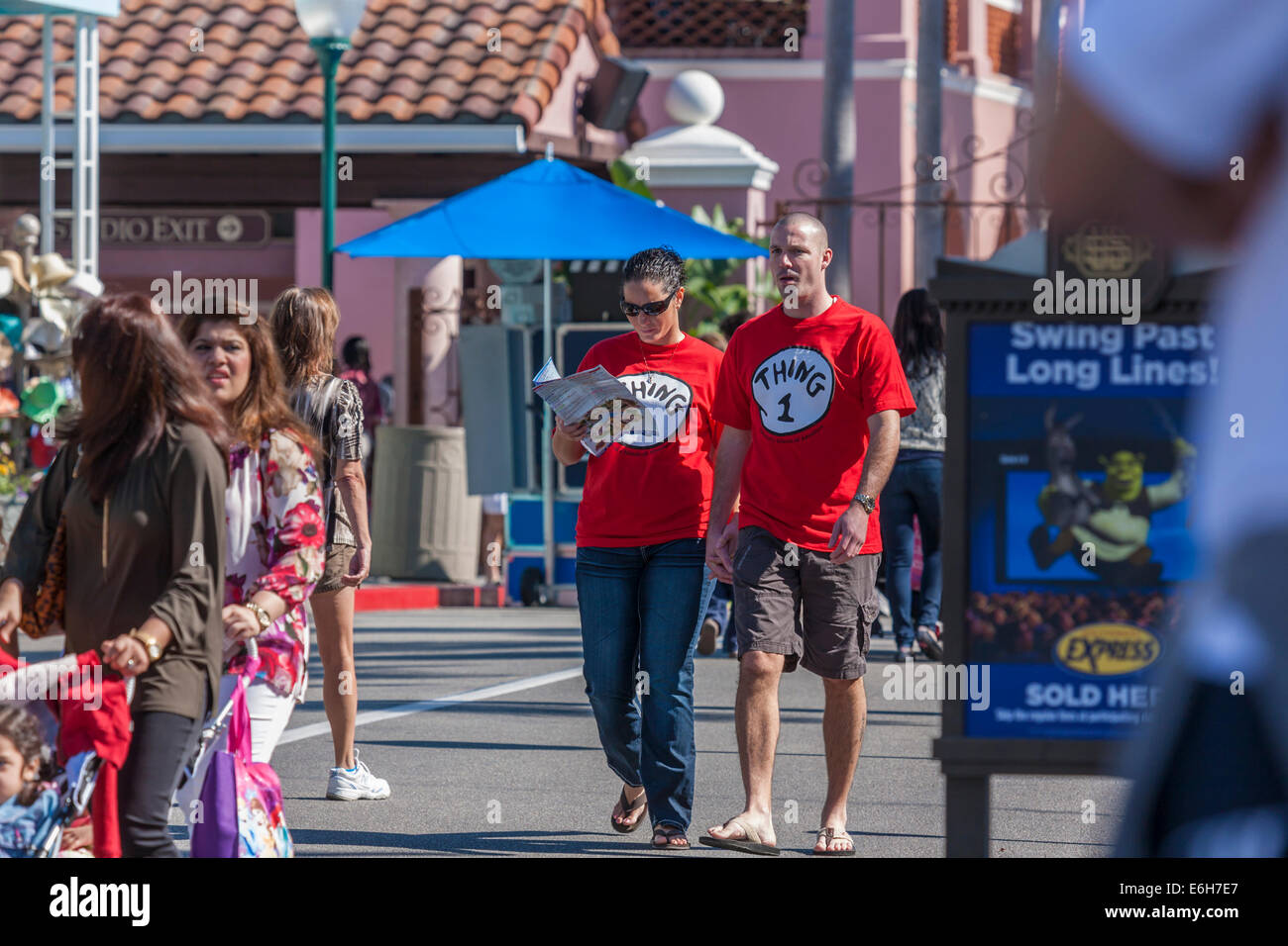 Young couple wearing Thing 1 and Thing 2 t-shirts walking on street in Universal Studios, Orlando - Stock Image