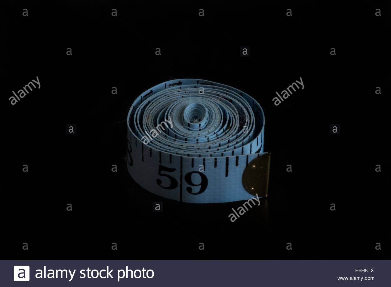 A rolled up tape measure displaying inches. - Stock Image
