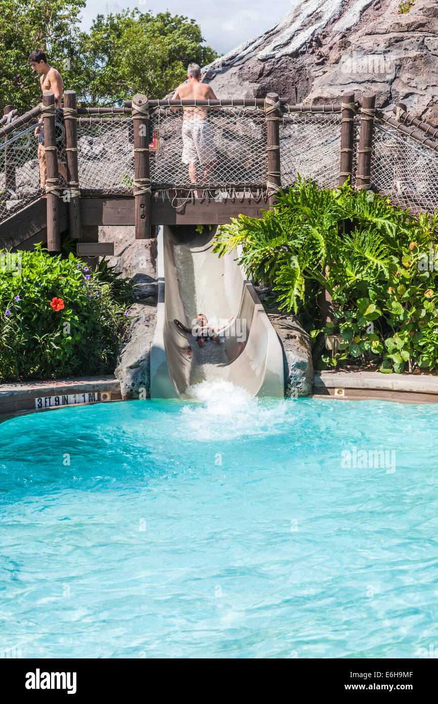 Child sliding out of the volcano at the Polynesian Resort swimming pool in Walt Disney World, Florida - Stock Image