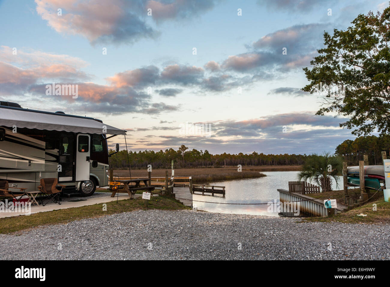 Motorhome set up for camping next to boat ramp for Indian Bayou at Avalon Landing RV Park in Pensacola, Florida - Stock Image