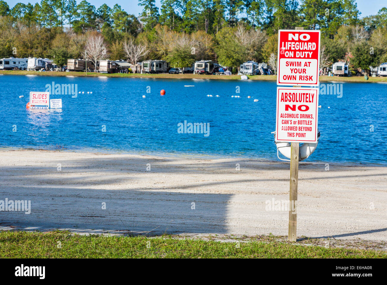 Signs warn of swimming at your own risk in lake at Flamingo Lake RV Resort in Jacksonville, Florida - Stock Image