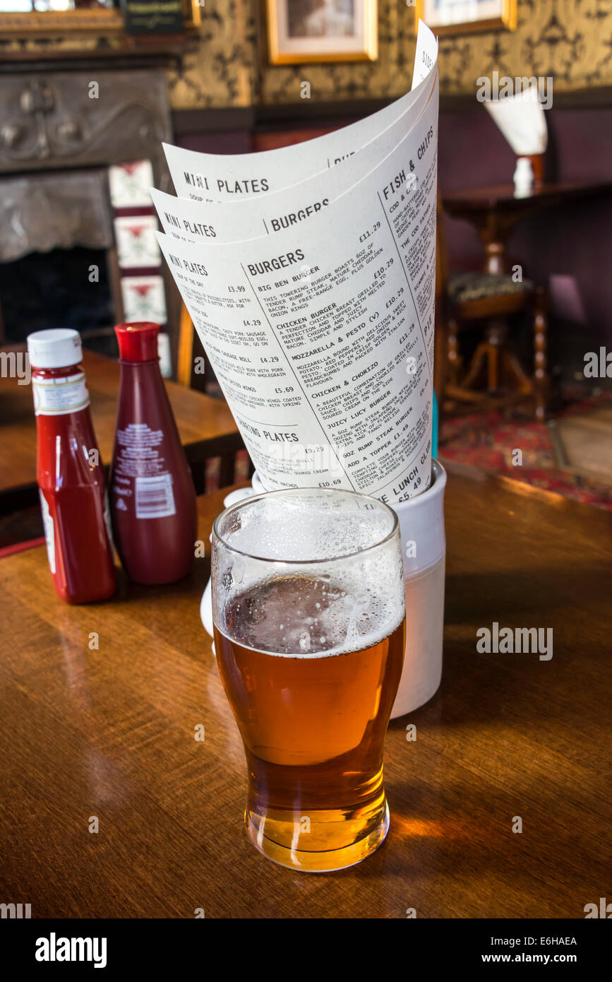A pint of beer in front of lunchtime menus in a traditional English pub - Stock Image