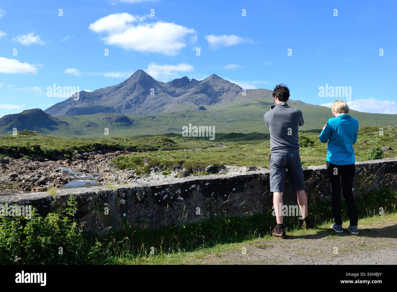 Tourists taking pictures of the Black Cuillin mountain range on Skye, Scotland, UK - Stock Image