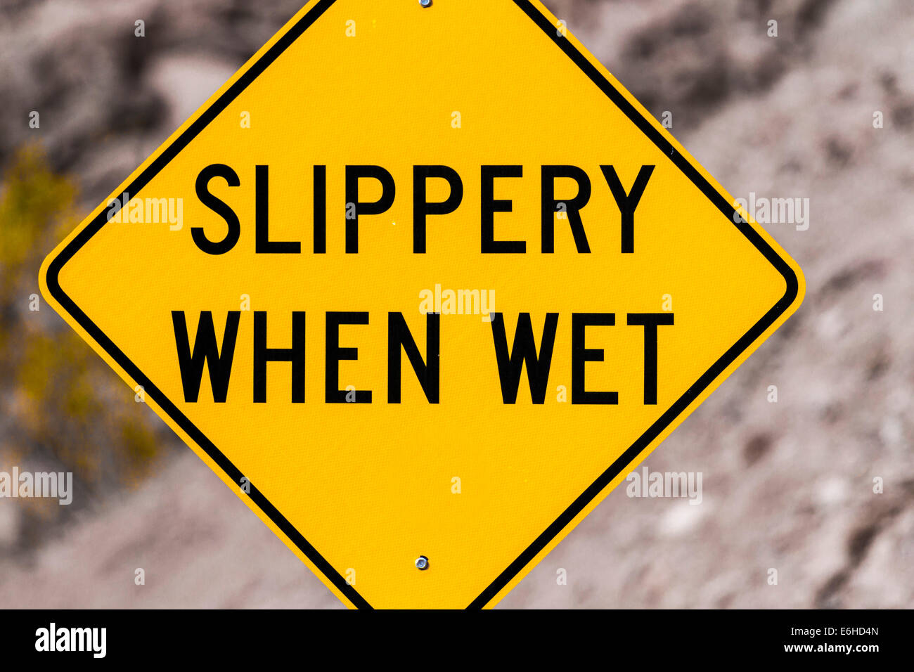 Sign warns that road ahead is 'Slippery When Wet' - Stock Image