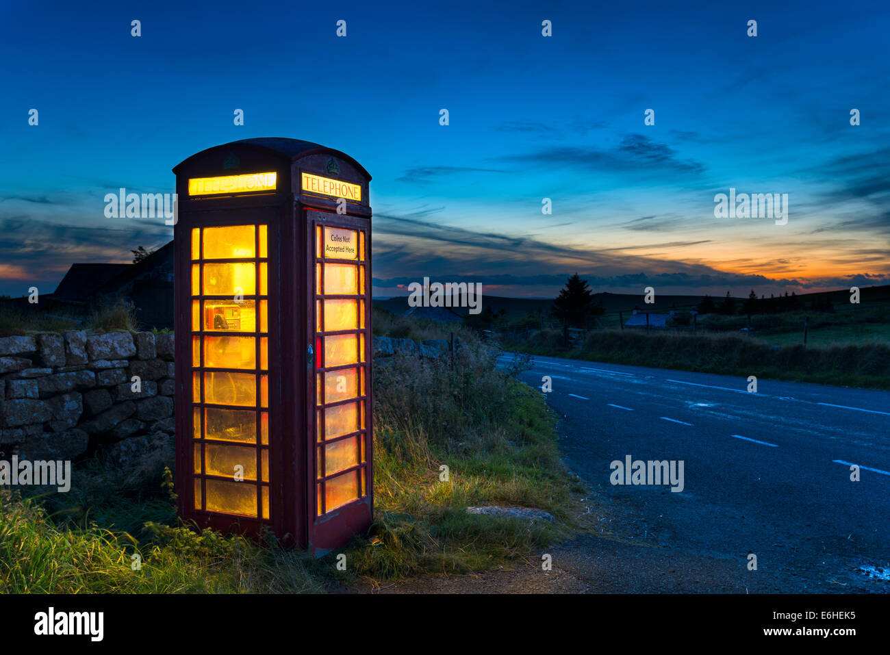 Old red phone box at dusk on a country road in Dartmoor, Devon - Stock Image