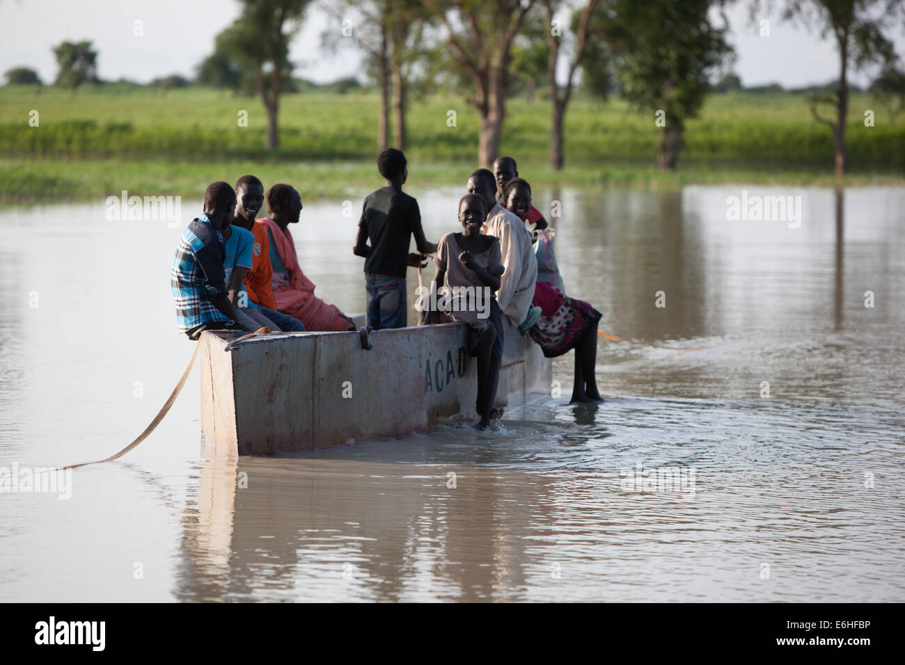Children use boat donated by ACAD to cross River Achok at Agok, Abyei province, Sudan / South Sudan. - Stock Image