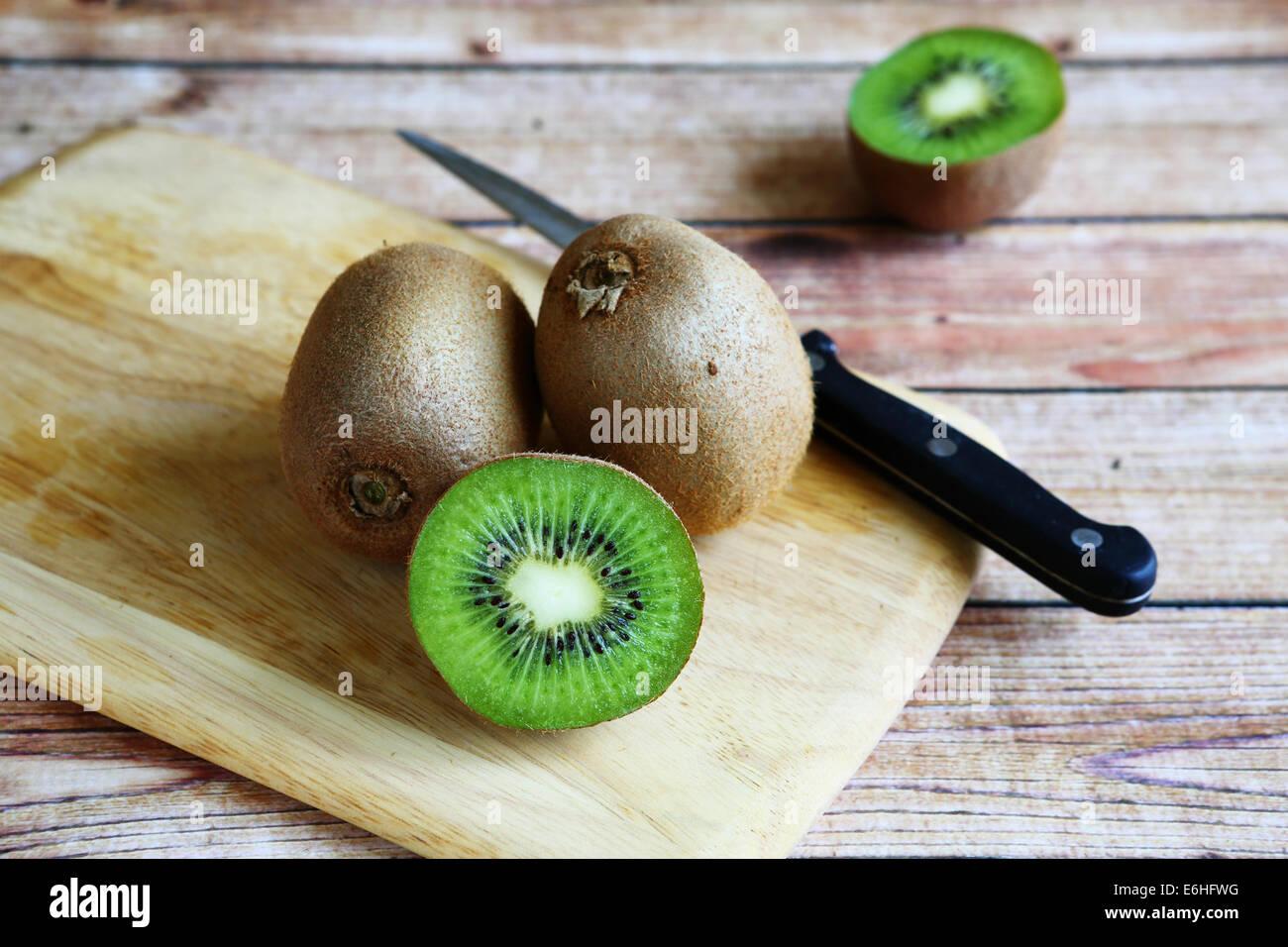 fresh kiwi on cutting board, food - Stock Image