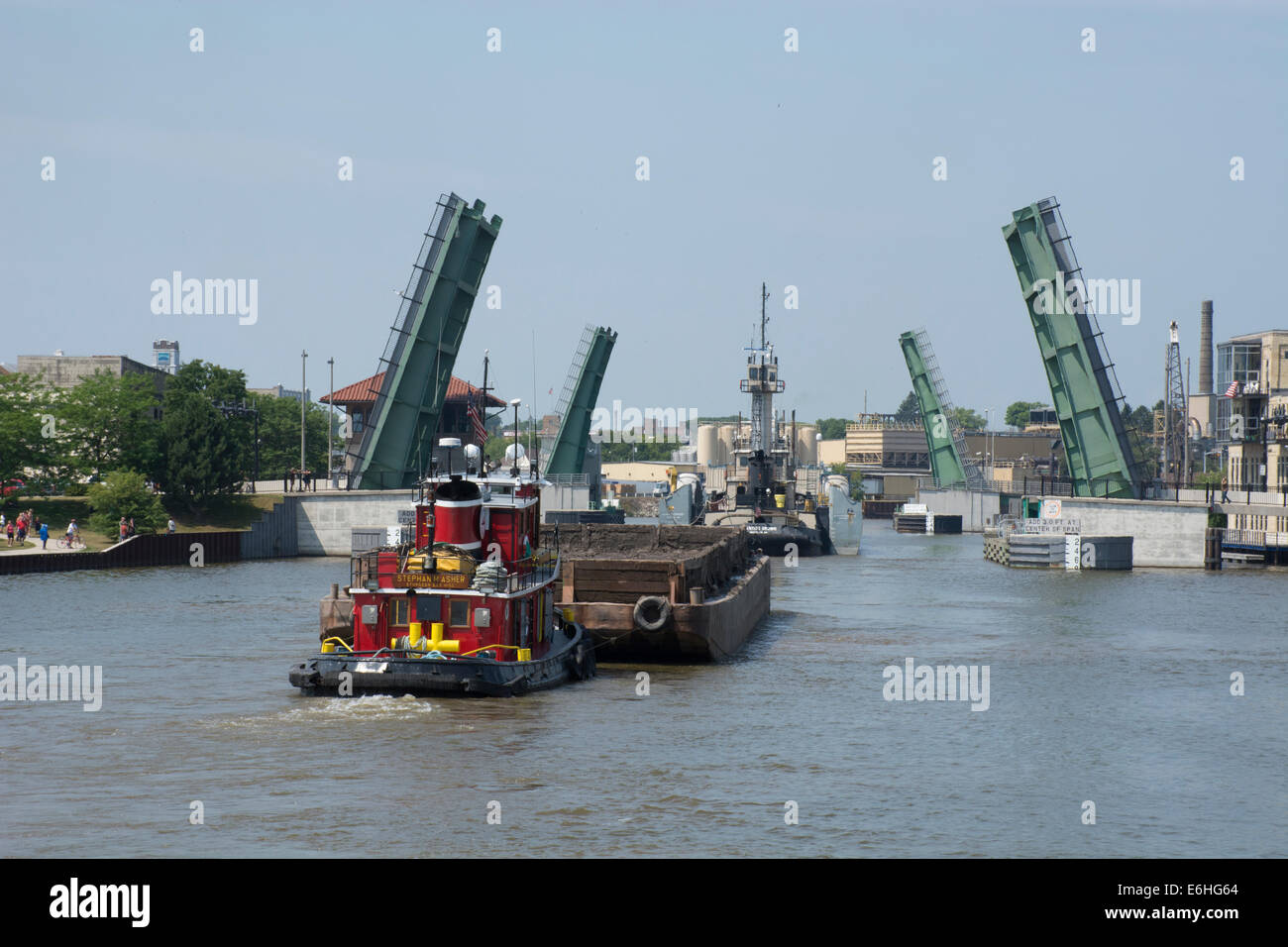 Wisconsin, Manitowoc. Manitowoc River. Tugboat and barge sailing up the Manitowoc River through downtown, lift bridges - Stock Image