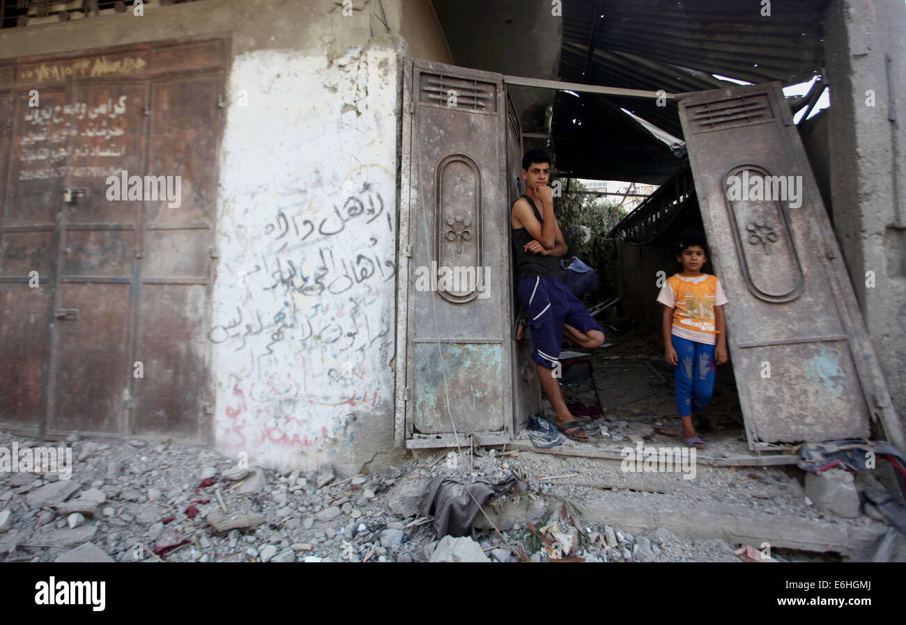 Gaza City, Gaza Strip, Palestinian Territory. 24th Aug, 2014. Palestinians stand on the remains of a house, which - Stock Image
