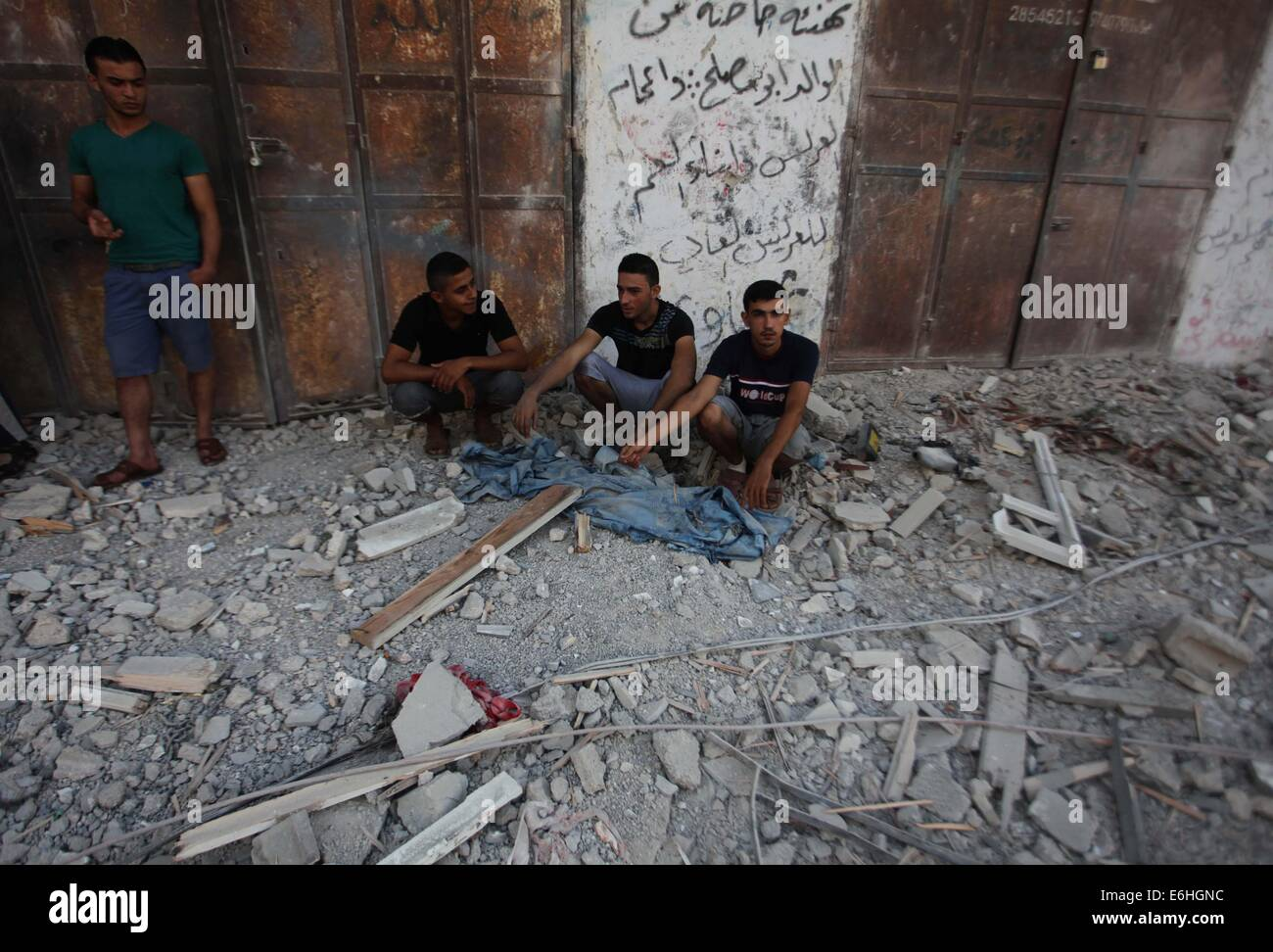 Gaza City, Gaza Strip, Palestinian Territory. 24th Aug, 2014. Palestinians sit on the remains of a house, which - Stock Image