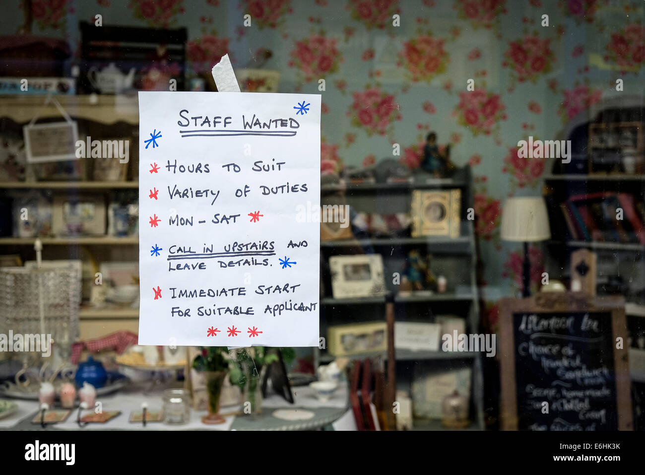 A hand written sign notice in a shop window advertising jobs staff vacancies. - Stock Image