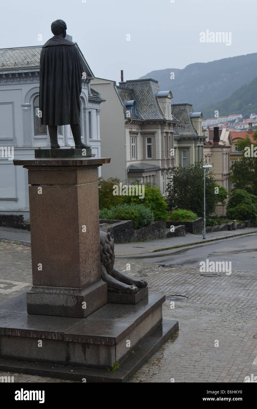 A statue (of Henrik Ibsen or Edward Grieg?) looks out from the national Theatre to a rainy day in Bergen. - Stock Image
