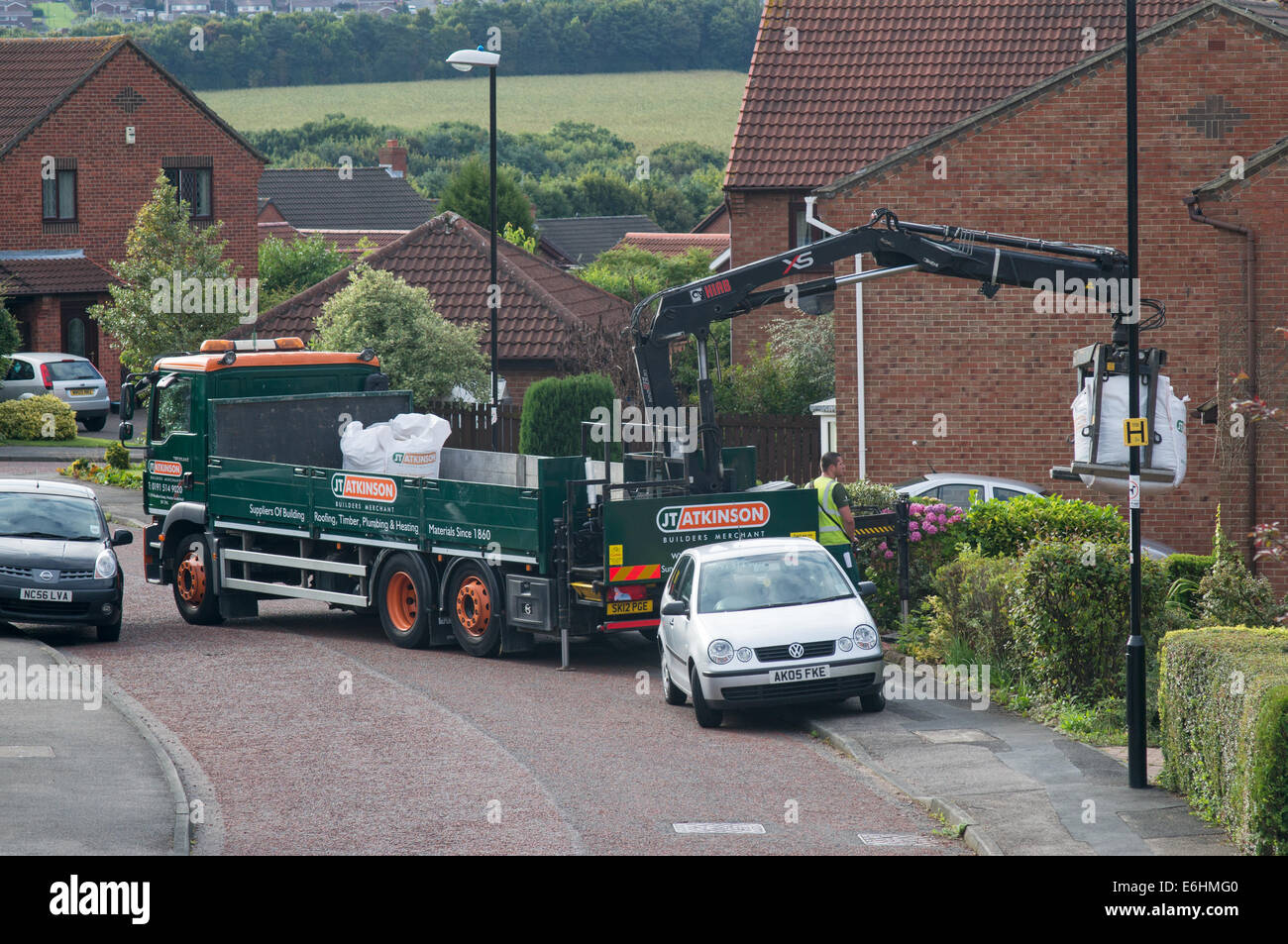 J T Atkinson builder's merchant's truck with HIAB XS tailift crane delivers to house in suburban street - Stock Image