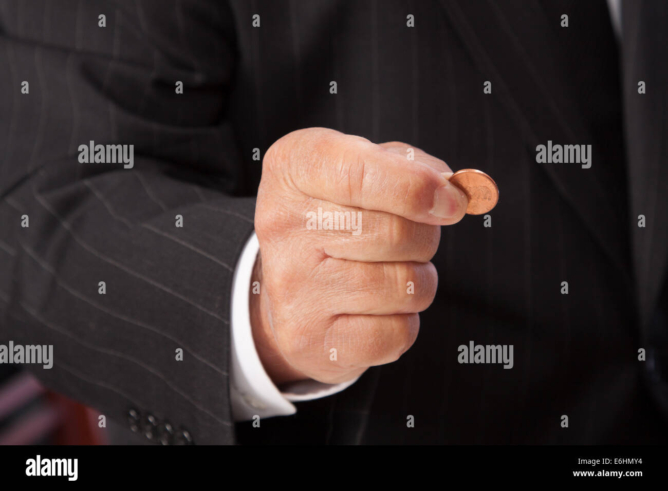 Man's hand pinching penny-horizontal, wearing pin-striped suit with white shirt cuff showing. - Stock Image