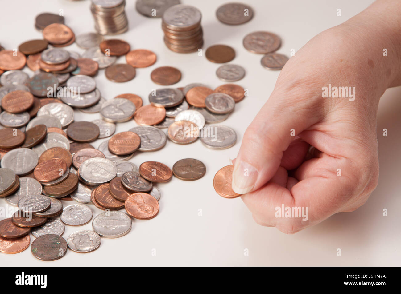 Woman's hand close up pinching a penny. Concept of retirement and not having enough money. Piles and stacks - Stock Image
