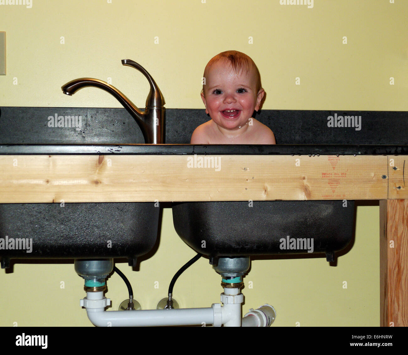 A smiling baby being washed in the sink - Stock Image