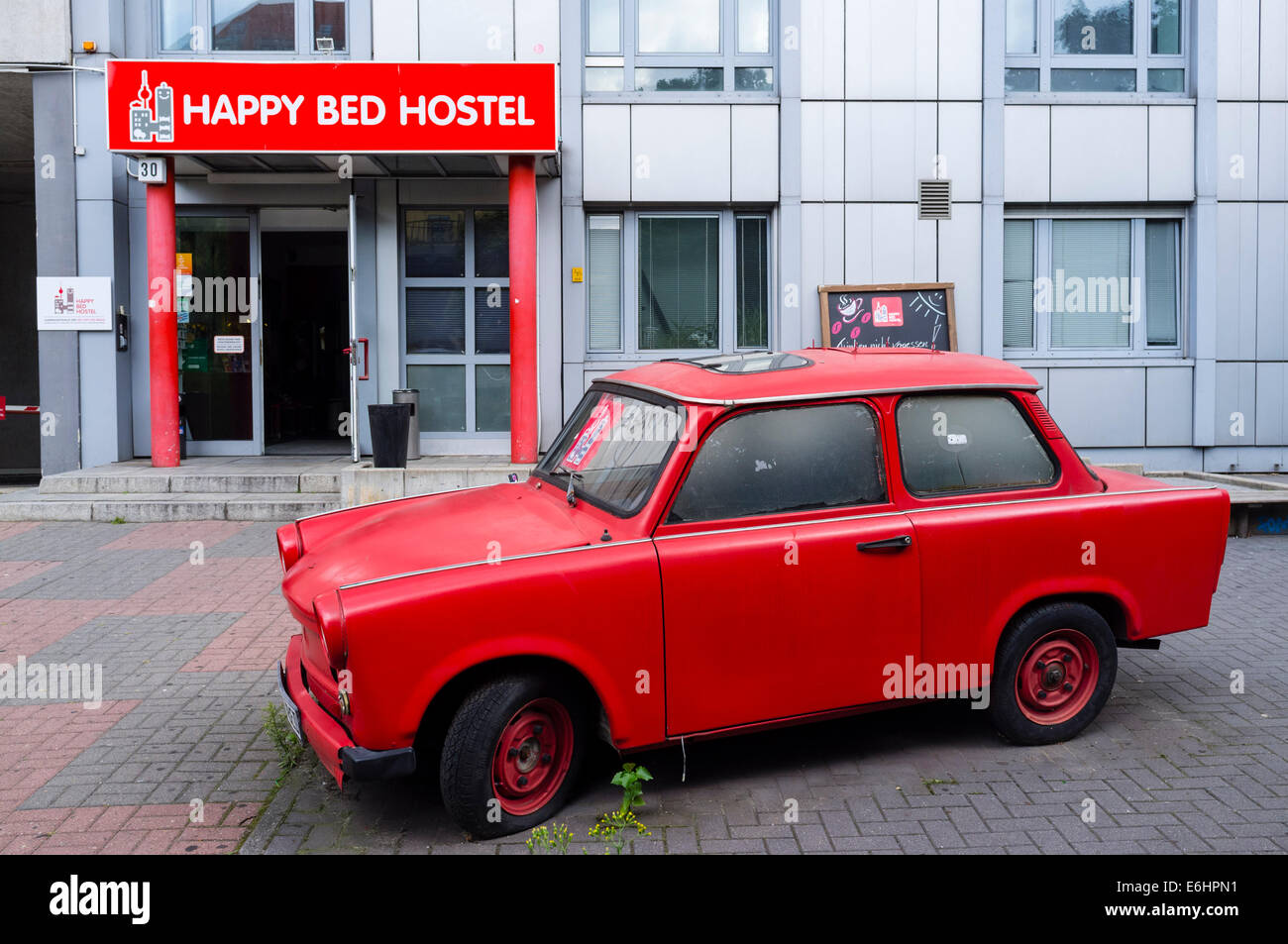 Exterior of Happy Bed  budget hostel with red East German Trabant car outside in Berlin Germany - Stock Image