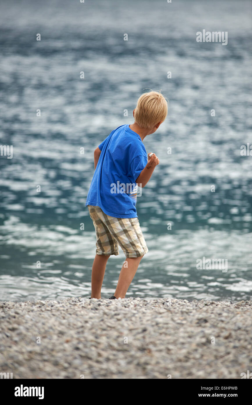Rear view of a child blond boy skimming pebbles into the sea summertime - Stock Image