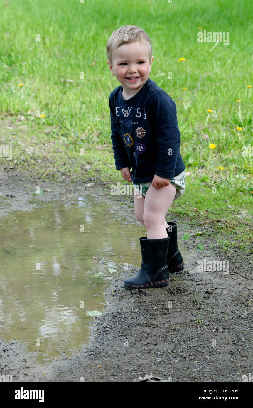 A young boy getting soaked running through a puddle - Stock Image