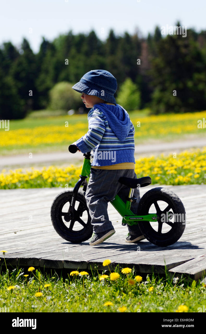 542bb0dac16 A two year old boy riding a Strider balance bike - Stock Image