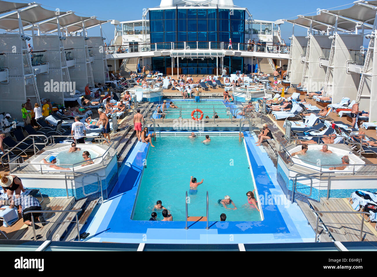 People in cruise ship liner swimming pools Jacuzzi & relaxing on sun lounger on sunbathing deck Mediterranean - Stock Image