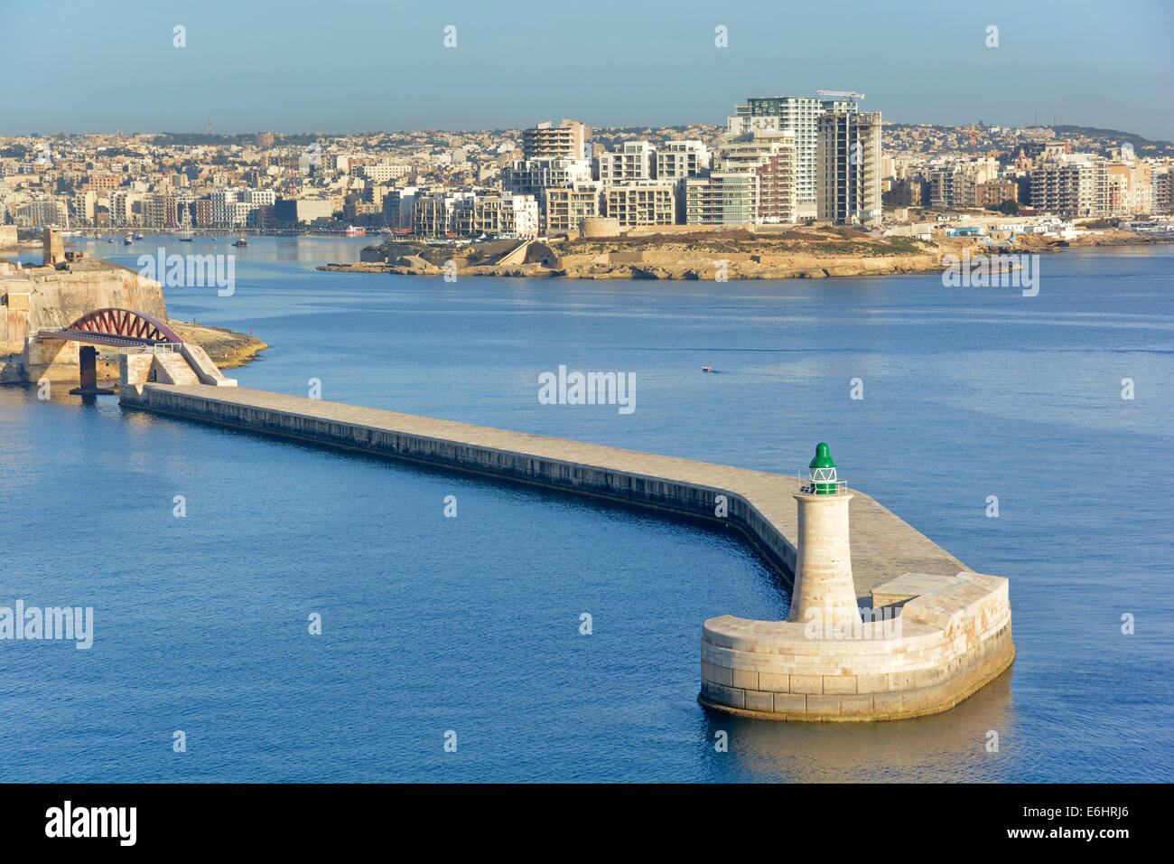 Green channel light on end of Grand Harbour wall with Saint Elmo Bridge and modern high rise building development - Stock Image
