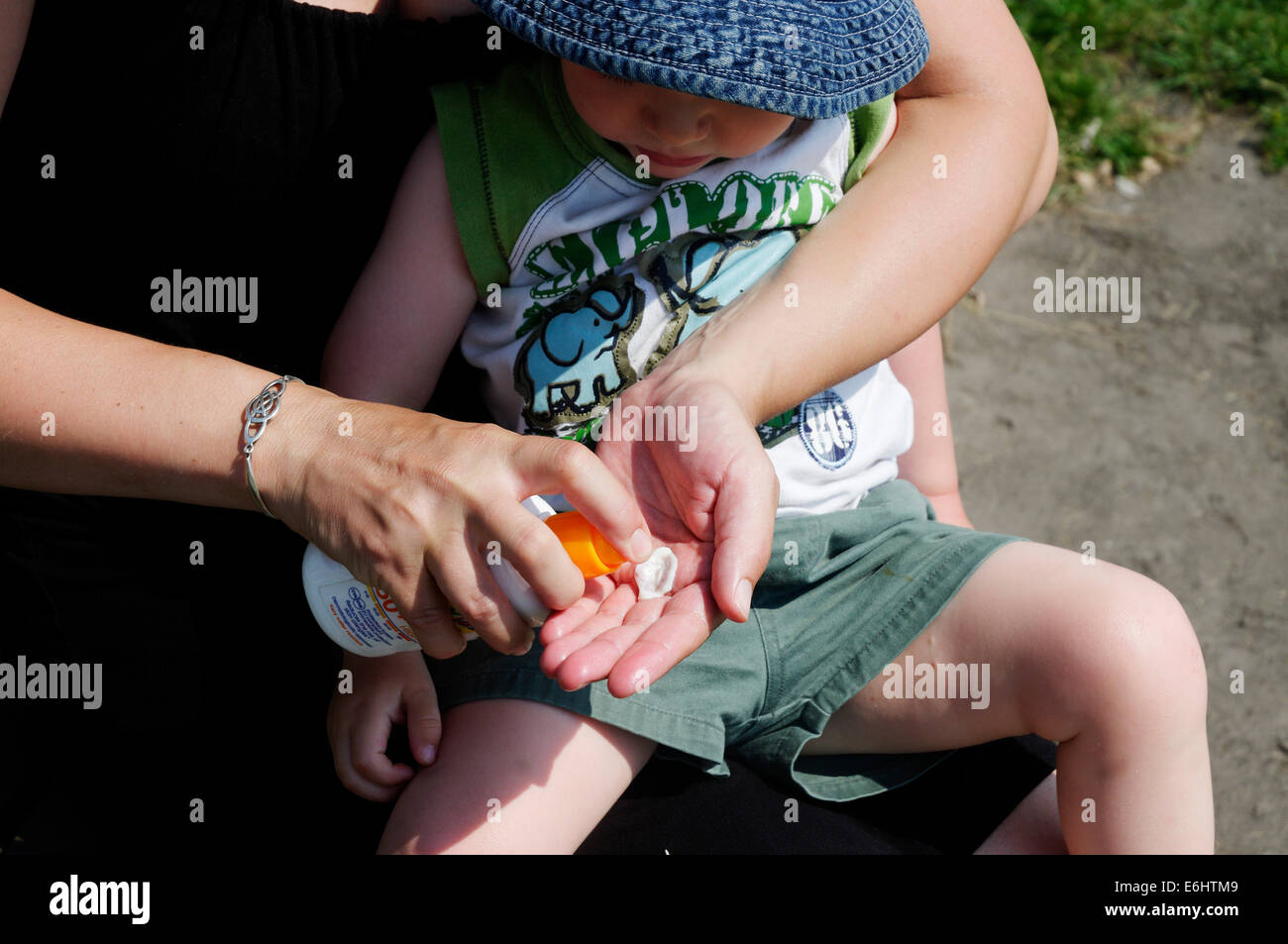 A mother spraying suncream on her two year old child - Stock Image