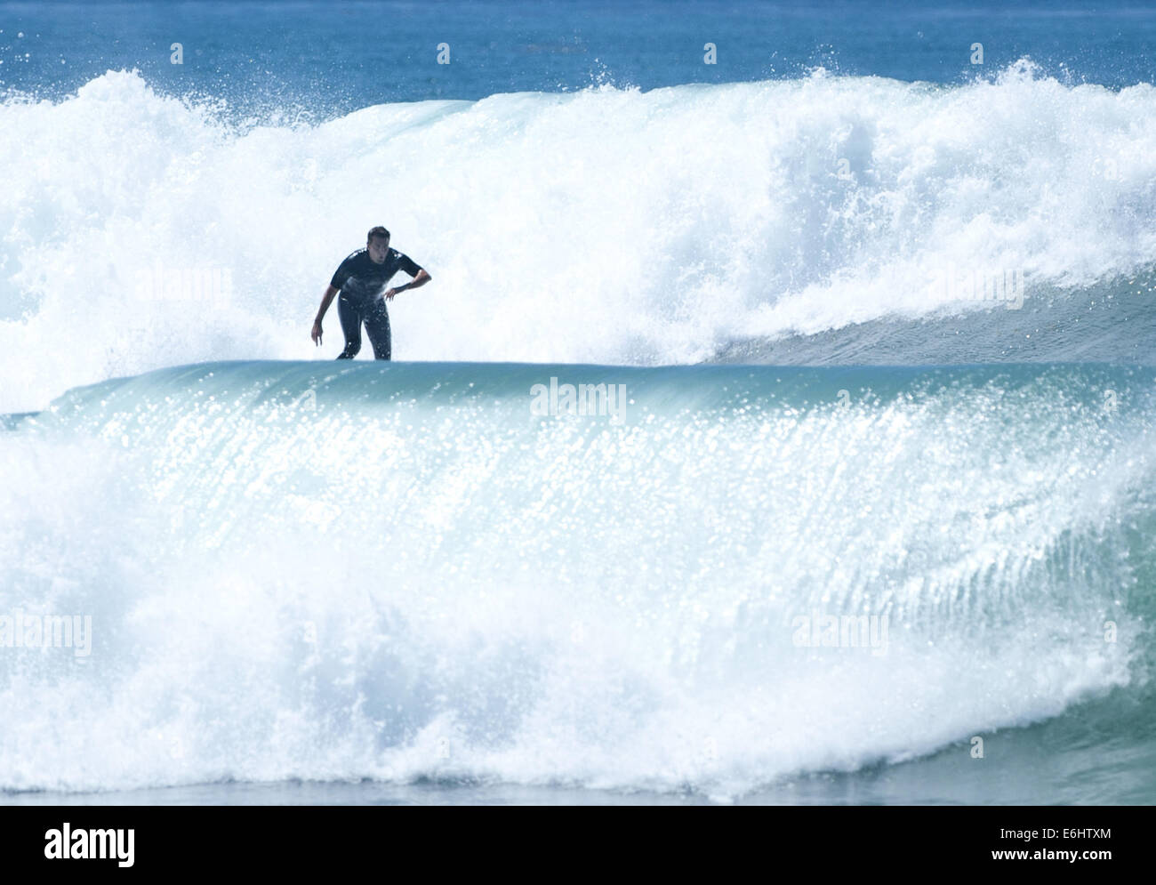 San Clemente, California, USA. 23rd Aug, 2014. A surfer plows through the white wash at the end of a long ride near - Stock Image
