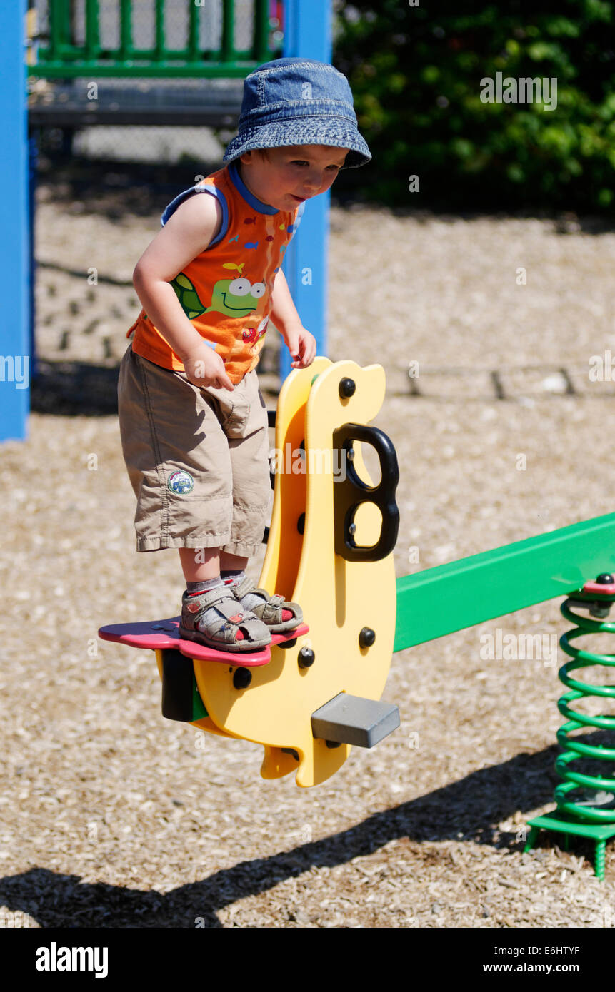 An excited young boy stood on a seesaw in a playground getting ready to jump - Stock Image