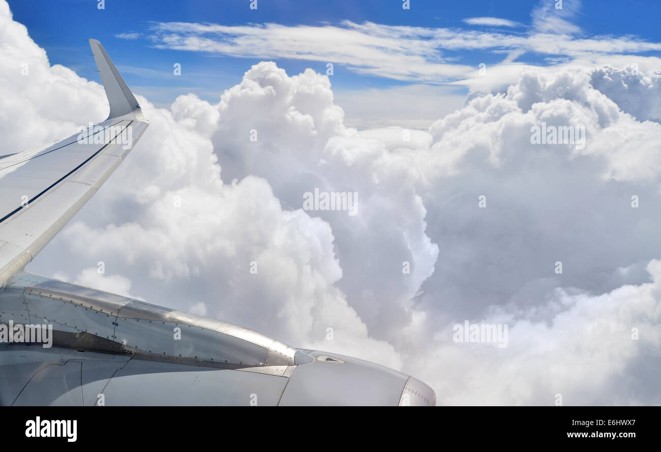 Airplane wing and engine flying high in the clouds. - Stock Image