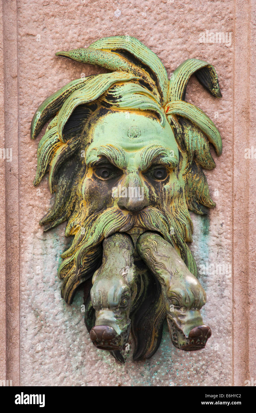 A fearsome face ornaments a spigot on the side of a fountain in the medieval city of Bruges, Belgium - Stock Image