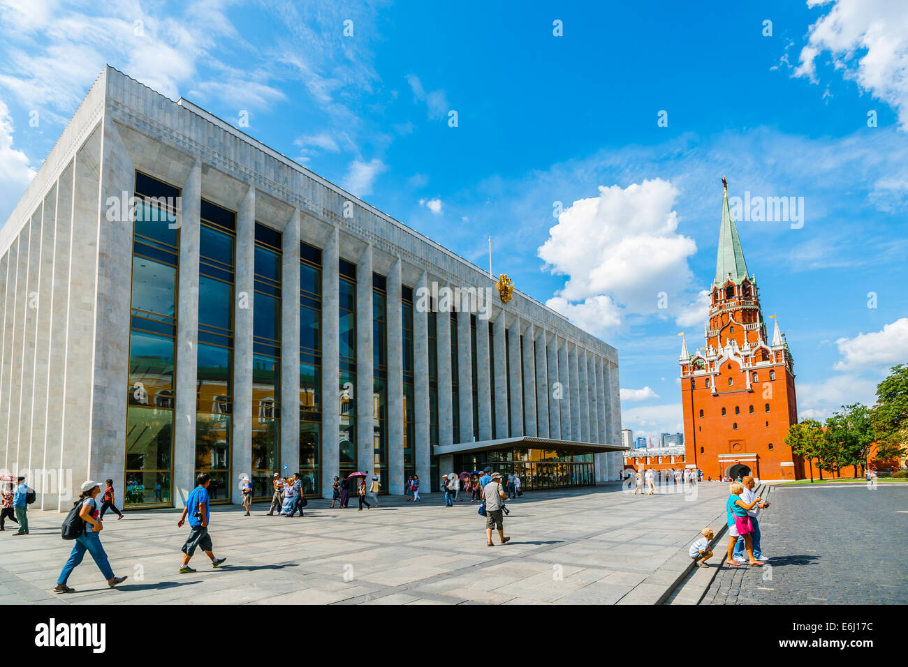 Moscow Kremlin Tour - 70. Tourists go past the State Kremlin Palace to the Trinity tower in order to leave the Kremlin - Stock Image