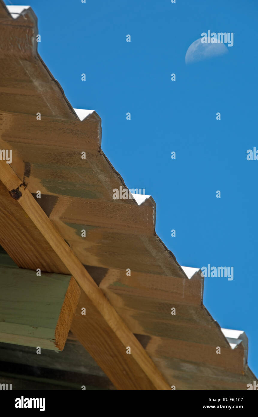 Metal tile house roof and moon in blue sky - Stock Image
